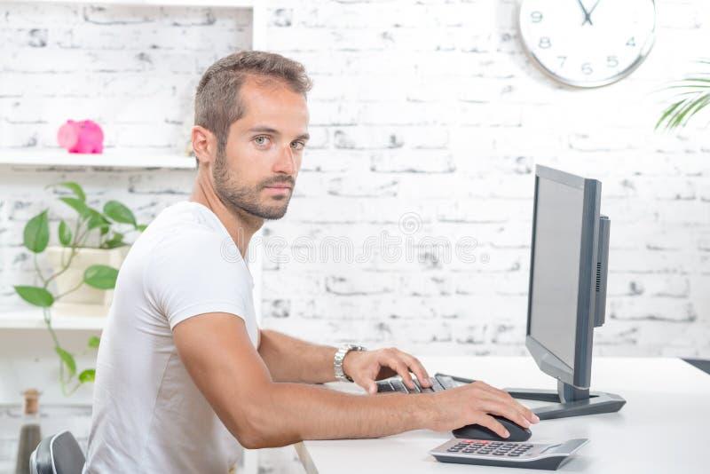 Het jonge uitvoerende werken met zijn computer stock foto