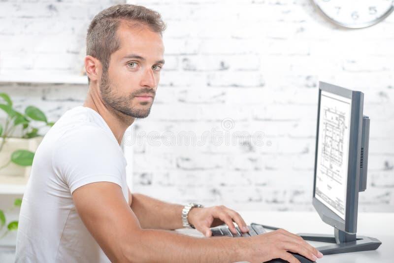 Het jonge uitvoerende werken met zijn computer stock afbeelding