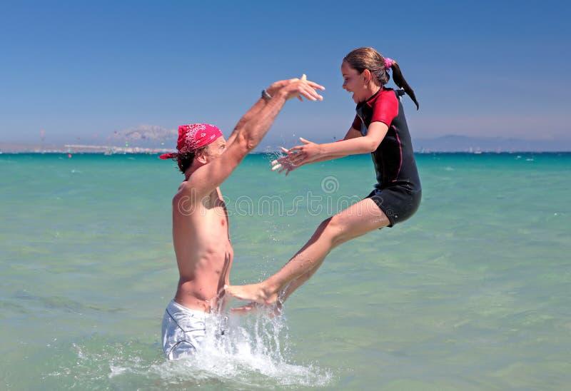 Het jonge vader en dochter spelen op strand in overzees royalty-vrije stock afbeeldingen