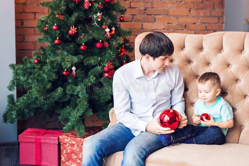 Het jonge vader spelen met zijn babyzoon op laag dichtbij Kerstboom royalty-vrije stock foto's