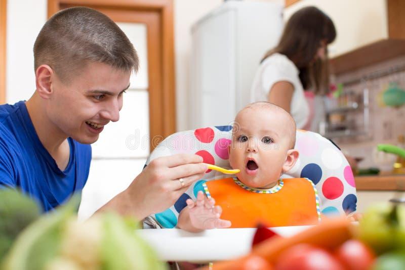Het jonge van het papa voedende baby en mamma koken bij keuken royalty-vrije stock afbeelding
