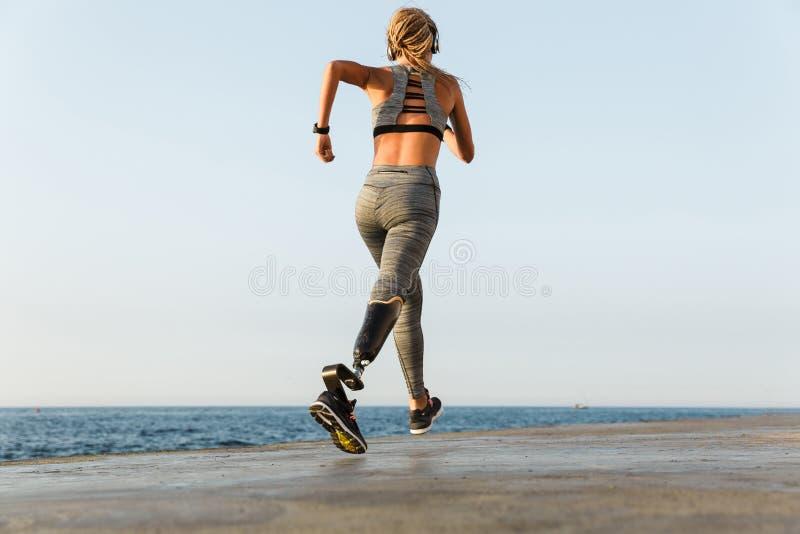 Het jonge verbazende gehandicapte sportenvrouw lopen stock foto