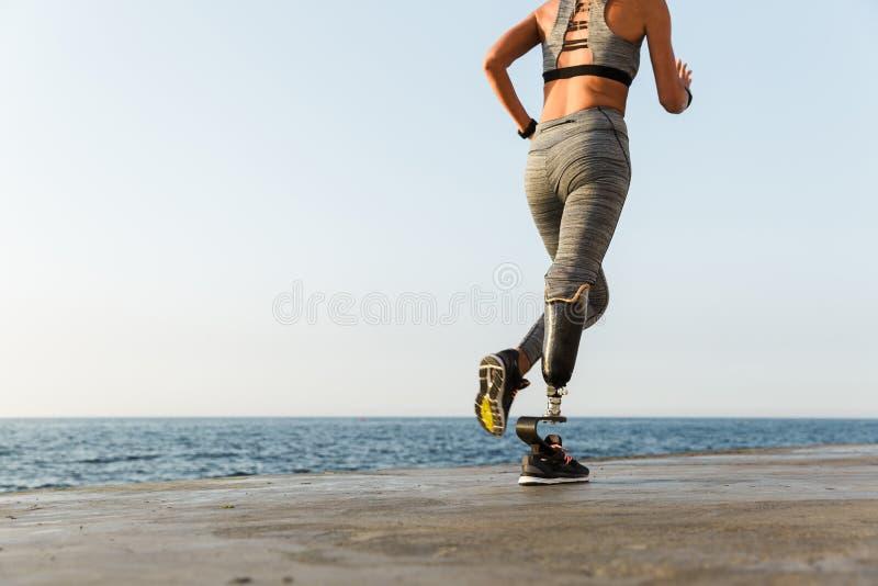 Het jonge verbazende gehandicapte sportenvrouw lopen stock foto's