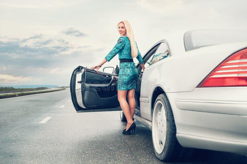 Het jonge verblijf van de blondevrouw dichtbij auto op eenzame weg stock foto's
