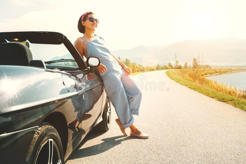 Het jonge verblijf van de vrouwen solo reiziger dichtbij cabriolet auto op schilderachtig royalty-vrije stock foto's