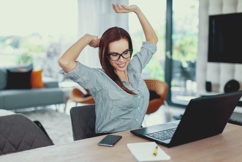 Het jonge vermoeide freelancer vrouw uitrekken zich bij laptop stock afbeeldingen