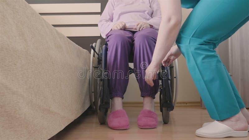 Het jonge verpleegster geven van oudere gehandicapte vrouw in rolstoel en overdrachten haar in bed stock videobeelden