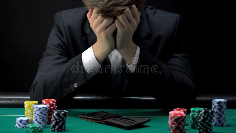Het jonge verwoeste spel van de zakenman verliezende pook bij casino, het gokken verslaving royalty-vrije stock foto's