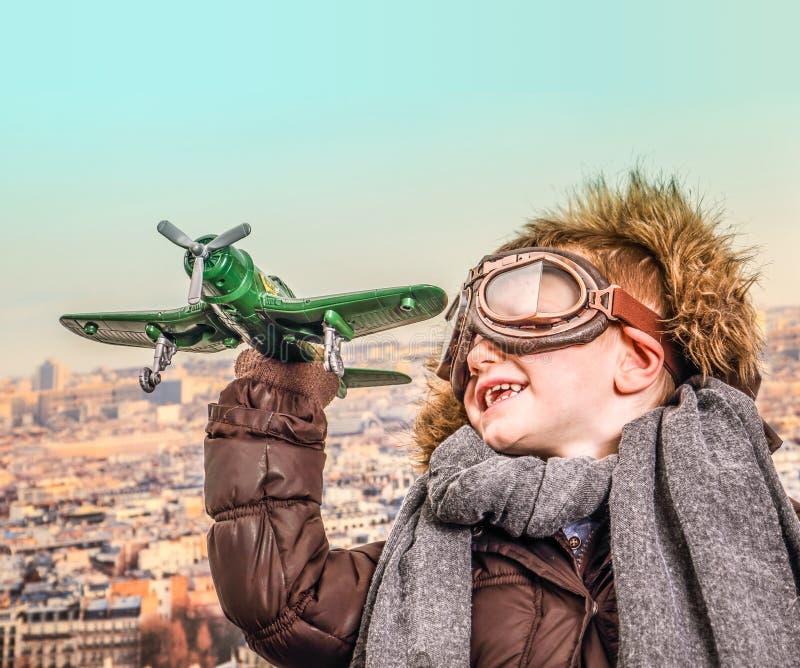 Het jonge vliegenier spelen met stuk speelgoed vliegtuig stock fotografie