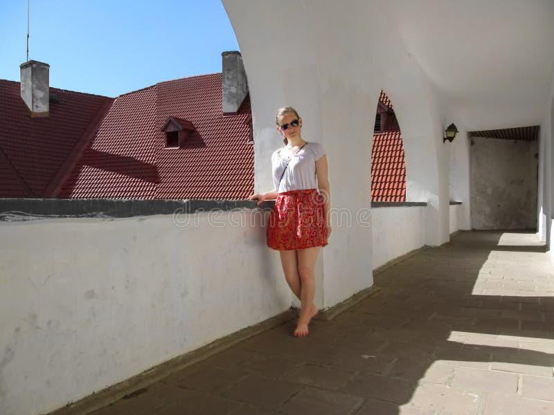 Het jonge volwassen blootvoetse meisje bevindt zich in de oude gang in het Kasteel Palanok stock fotografie