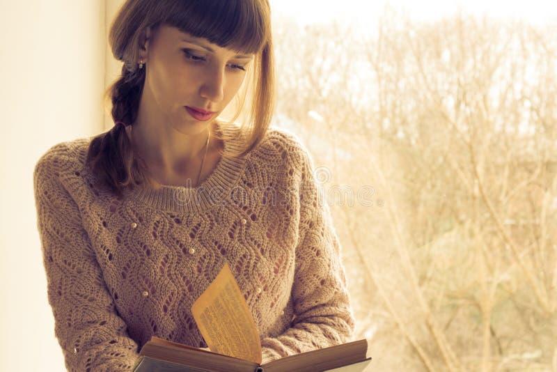 Het jonge volwassen boek van de vrouwenlezing dichtbij het venster stock foto