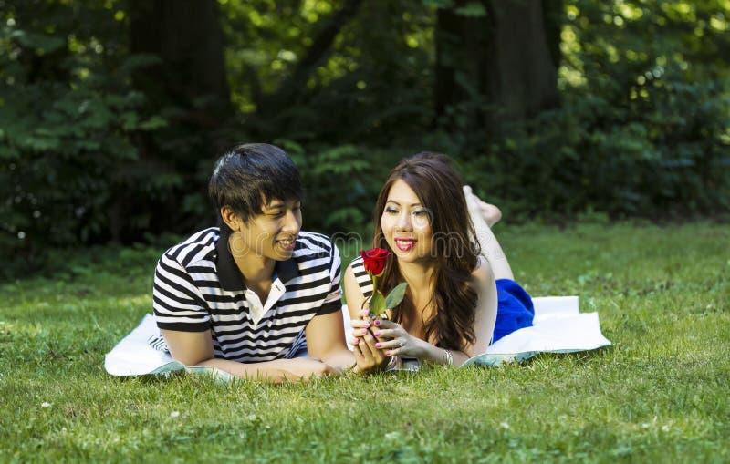 Het jonge Volwassen Paar geniet van bekijkend Enige Rood toenam stock foto