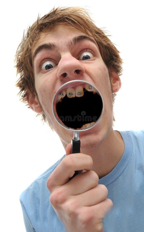 Het jonge volwassen vergrootglas van de mensenholding aan mond stock foto