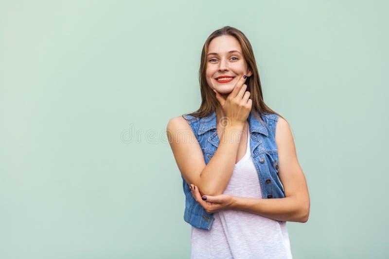 Het jonge volwassen vrouwelijke model stellen in studio Vrij toevallig meisje met sproeten, die over lichtblauwe achtergrond stel stock fotografie