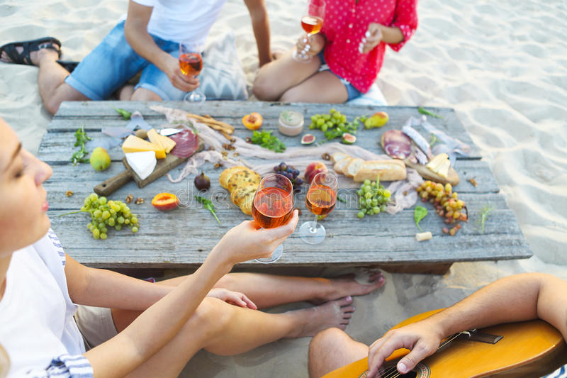Het jonge vrienden drinken nam wijn op de picknick van het de zomerstrand toe stock afbeeldingen