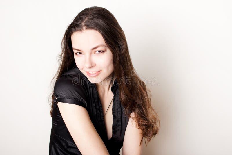 Het jonge vriendschappelijke donkerbruine glimlachen Portret van een jonge zekere vrouw, royalty-vrije stock fotografie