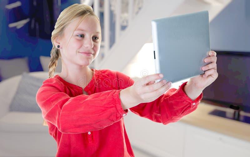 Het jonge vrij blonde meisje maakt een selfie thuis met haar tablet royalty-vrije stock afbeelding