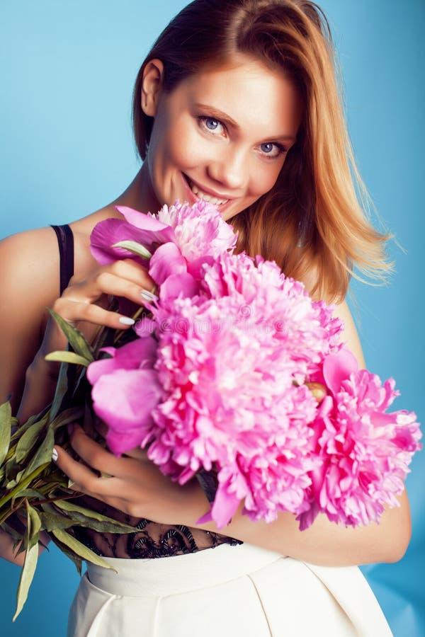 Het jonge vrij blonde meisje stellen op blauwe achtergrond, het boeket van de de dameholding van de manierstijl van roze piony bl royalty-vrije stock afbeelding