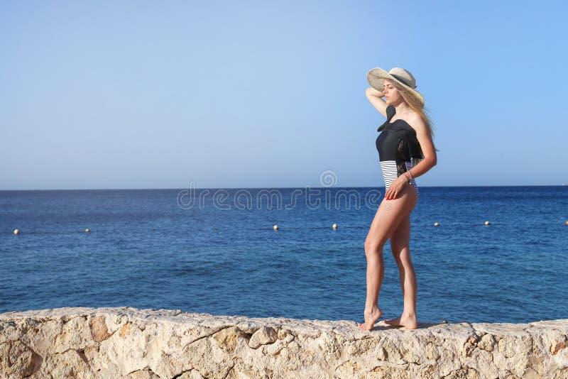 Het jonge vrij hete sexy aantrekkelijke meisje ontspannen in zwempak op stenen met blauwe overzees en hemel op achtergrond De vak royalty-vrije stock foto's