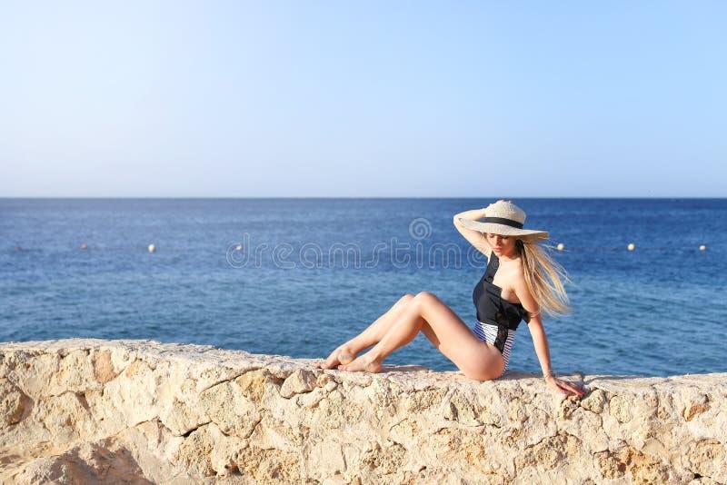 Het jonge vrij hete sexy vrouw ontspannen in zwempak op stenen met blauwe overzees en hemel op achtergrond De vakantieconcept van royalty-vrije stock foto