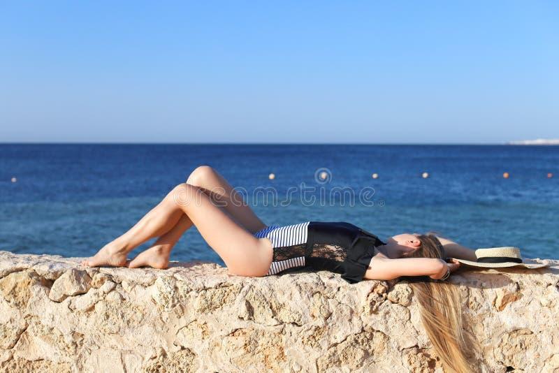 Het jonge vrij hete sexy vrouw ontspannen in zwempak op stenen met blauwe overzees en hemel op achtergrond De vakantieconcept van royalty-vrije stock foto's