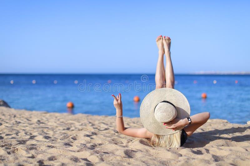 Het jonge vrij hete sexy vrouw ontspannen in zwempak op stenen met blauwe overzees en hemel op achtergrond De vakantieconcept van royalty-vrije stock afbeelding