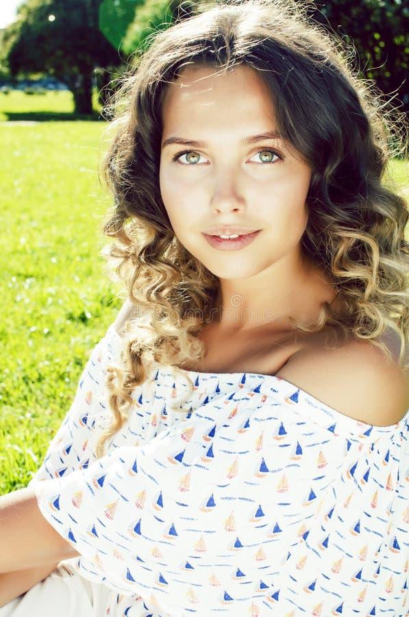 Het jonge vrij krullende meisje glimlachen vrolijk op groen gras, het concept van levensstijlmensen royalty-vrije stock fotografie