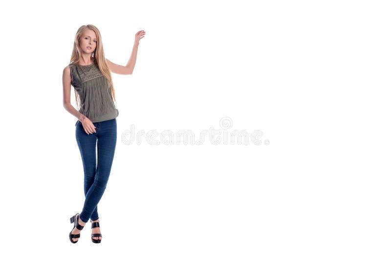 Het jonge vrij langharige blondevrouw stellen in vrijetijdskleding voorstellen, die iets tonen om geïsoleerde ruimte te kopiëren stock fotografie
