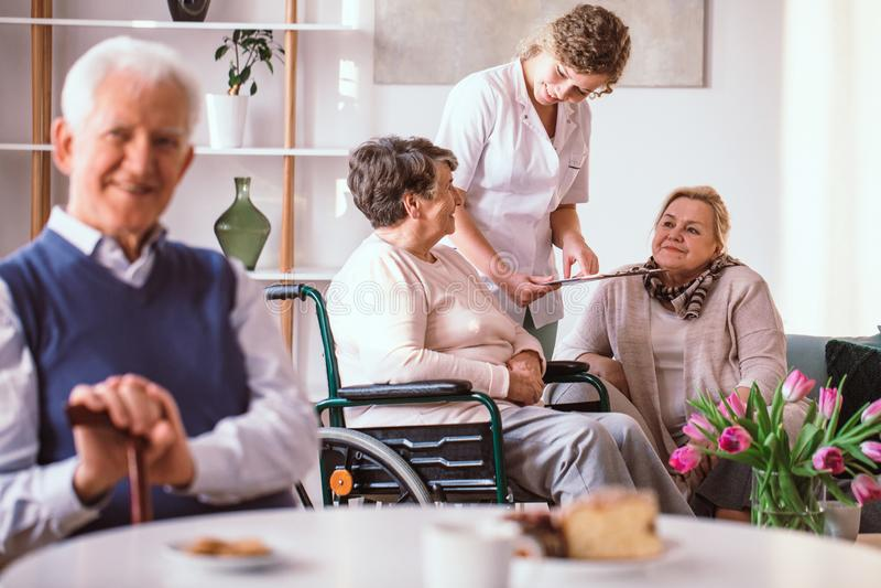 Het jonge vrijwilligers spreken met bejaarde dame op de rolstoel in het pensioneringshuis royalty-vrije stock foto
