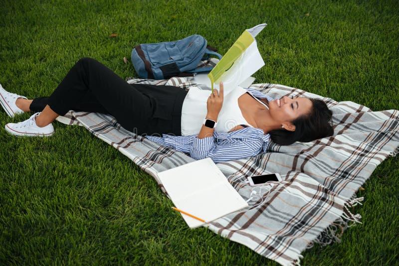 Het jonge vrolijke Aziatische vrouwelijke boek van de studentenlezing, die op g liggen stock afbeelding