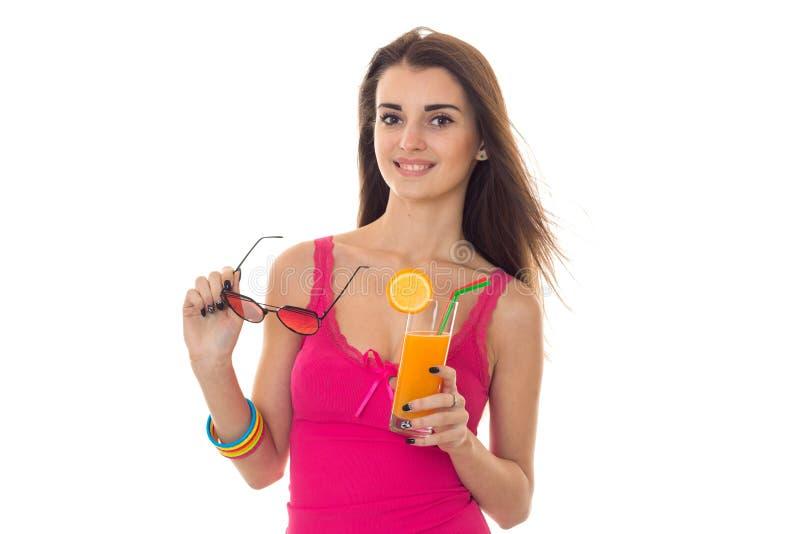 Het jonge vrolijke donkerbruine meisje in roze overhemd drinkt oranje cocktail glimlachend op camera en start geïsoleerde zonnebr royalty-vrije stock fotografie