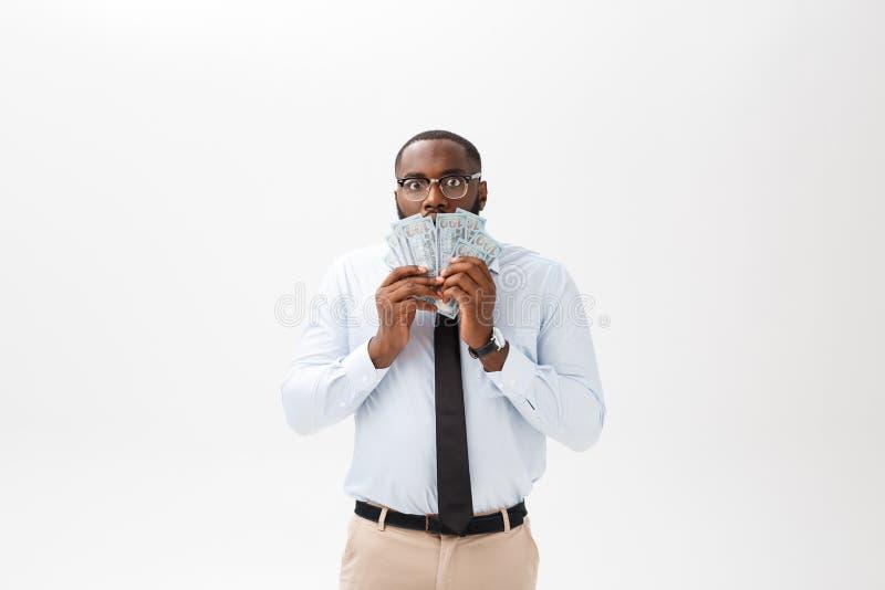 Het jonge vrolijke zwarte contante geld van de zakenmanholding op zijn die gezicht bij geld op wit wordt geïsoleerd royalty-vrije stock afbeeldingen