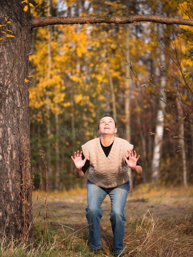 Het jonge vrouw bekijken omhoog de tak en treft te springen voorbereidingen stock afbeelding