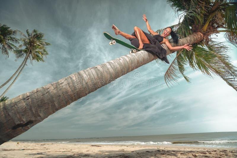 Het jonge vrouw berijden onderaan kokospalm stock afbeeldingen