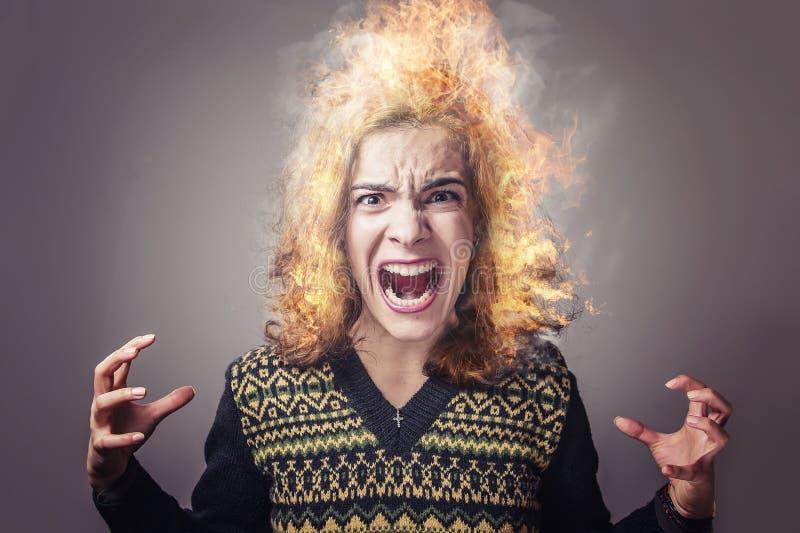 Het jonge vrouw branden met woede stock afbeelding