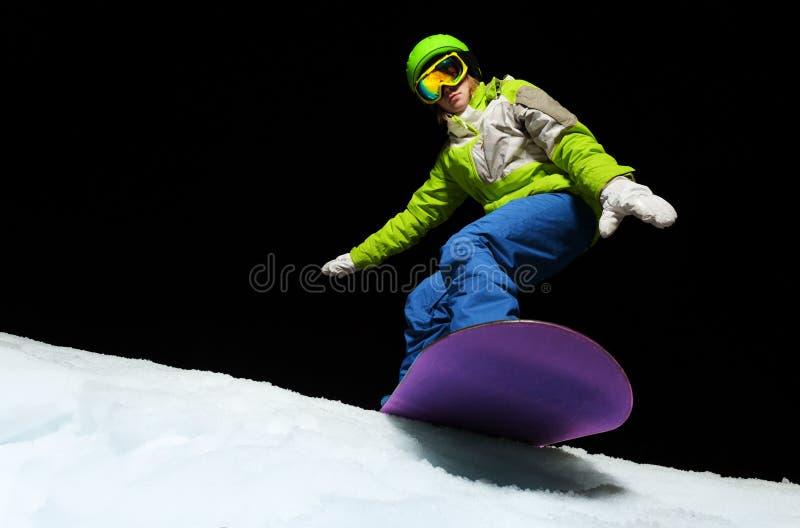 Het jonge vrouw in evenwicht brengen met handen op snowboard stock foto