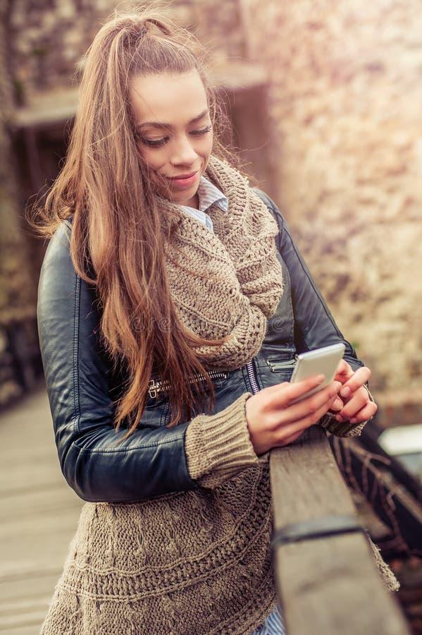 Het jonge vrouw gebruiken mobiel op de vesting royalty-vrije stock afbeelding