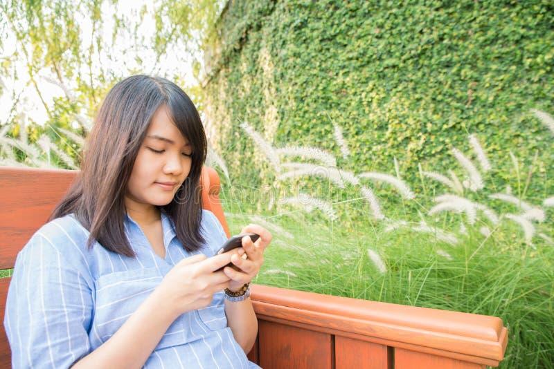 Het jonge vrouw glimlachen en de texting zitting van de celtelefoon op een parkbank in de herfst of daling stock afbeelding