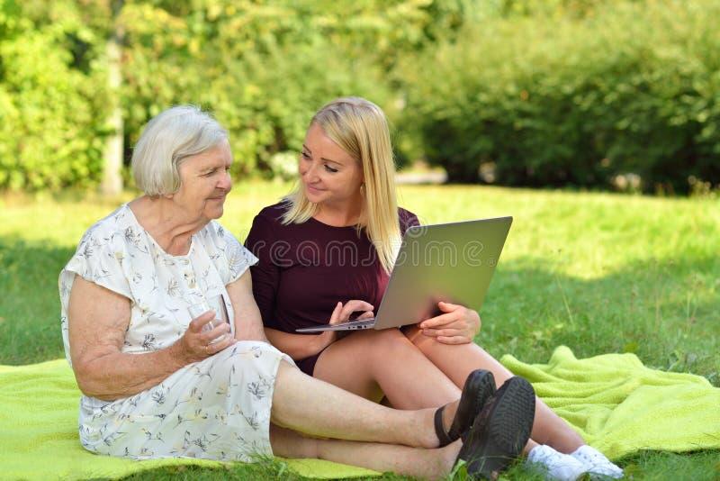 Het jonge vrouw helpen bejaarden om laptop te gebruiken royalty-vrije stock fotografie