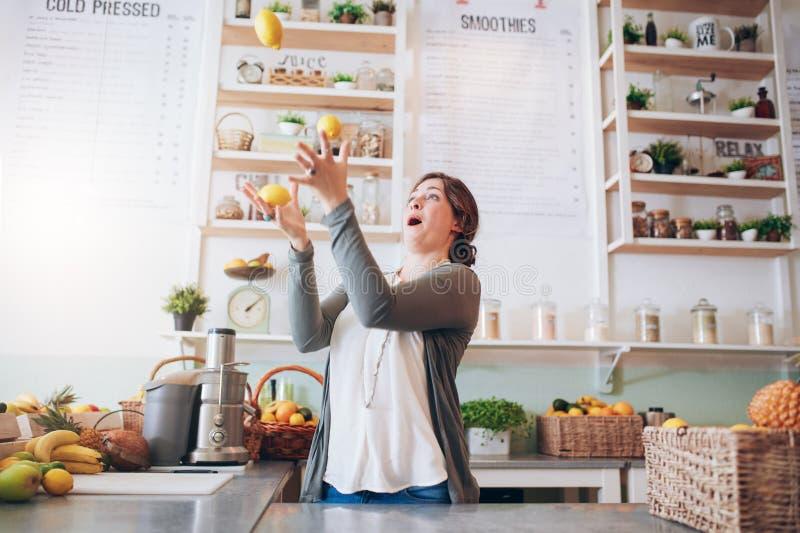 Het jonge vrouw jongleren met met citroen bij sapbar stock fotografie