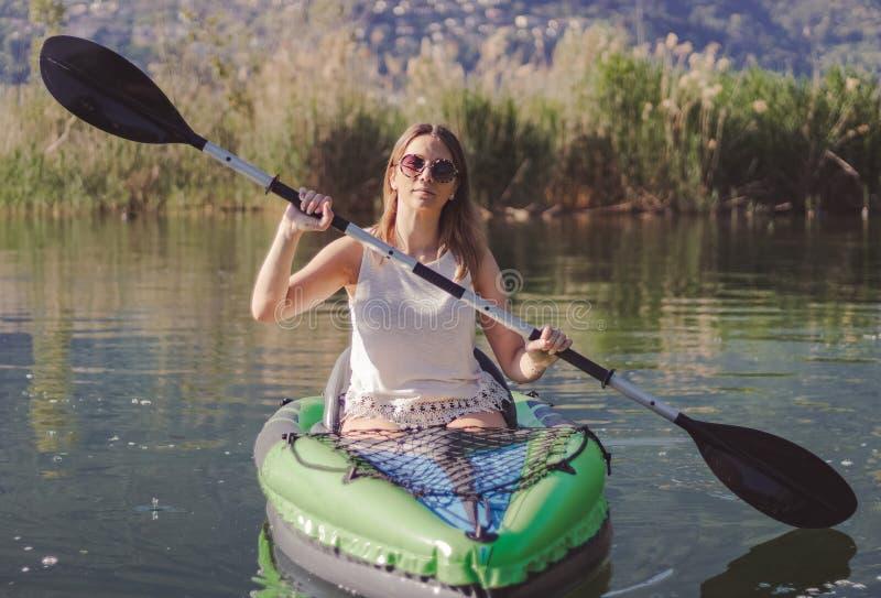 Het jonge vrouw kayaking op het meer stock fotografie