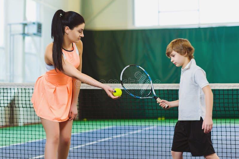 Het jonge vrouw of kind van het busonderwijs hoe te om tennis op een hof te spelen binnen stock afbeelding