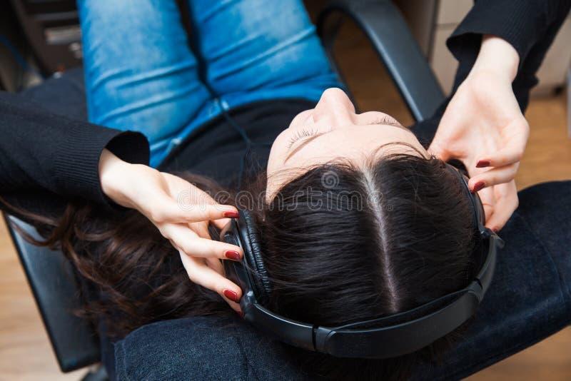 Het jonge vrouw koelen thuis in hoofdtelefoons Ontspan met muziek stock fotografie