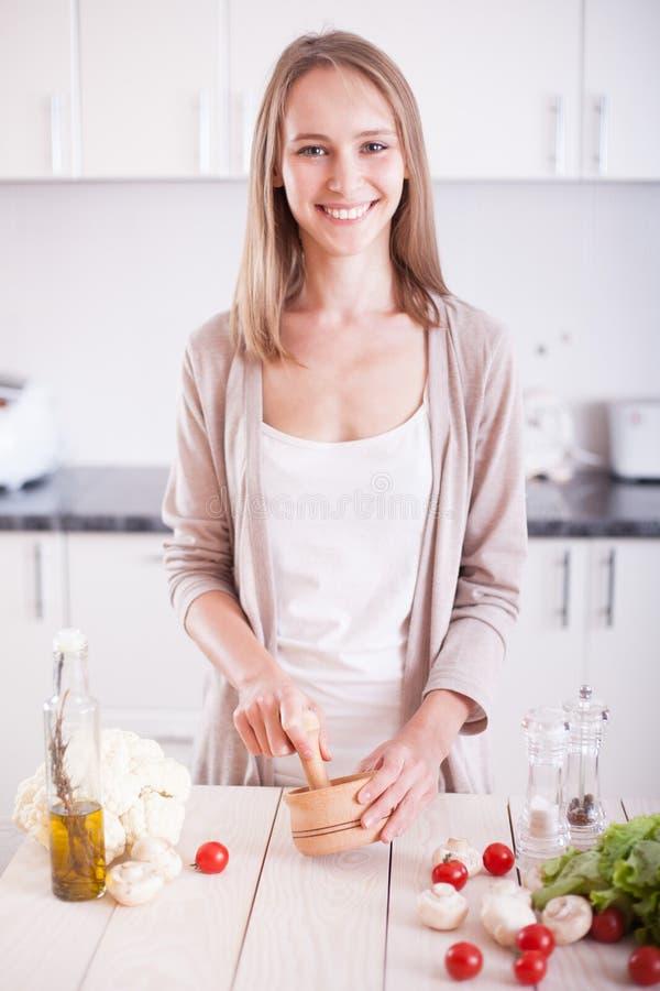 Het jonge vrouw koken in de keuken royalty-vrije stock afbeeldingen
