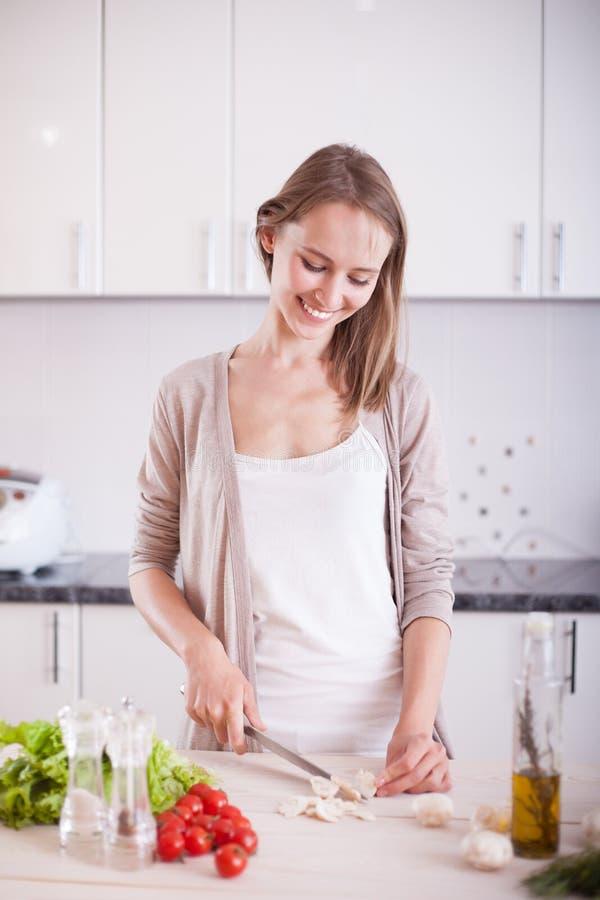 Het jonge vrouw koken in de keuken stock foto's