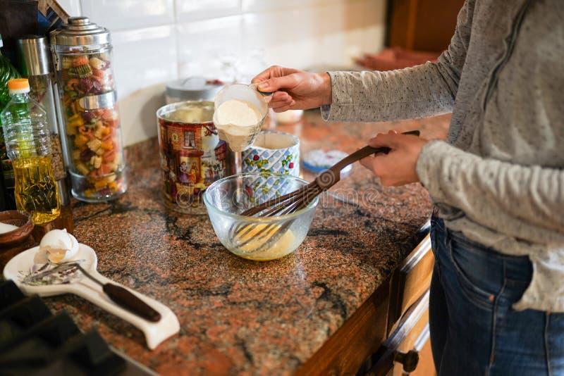 Het jonge vrouw koken in de keuken eieren in bloem op de lijst Modieuze moderne keuken kook een maaltijd in zonnige warme dag stock foto's