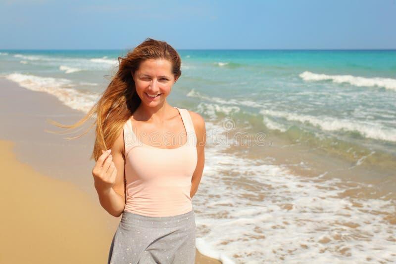 Het jonge vrouw loensen één oog, als sterke zon glanst op haar bij het strand, overzees op achtergrond royalty-vrije stock foto's