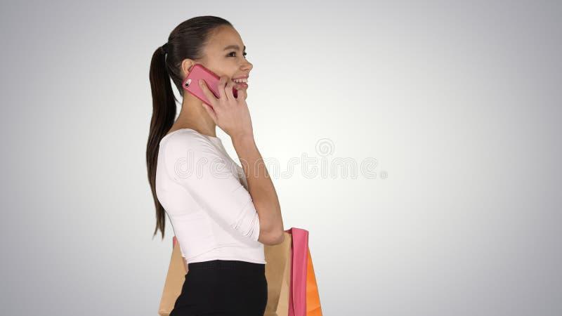 Het jonge vrouw lopen met het winkelen doet het spreken op mobiele telefoon op gradiëntachtergrond in zakken royalty-vrije stock afbeeldingen