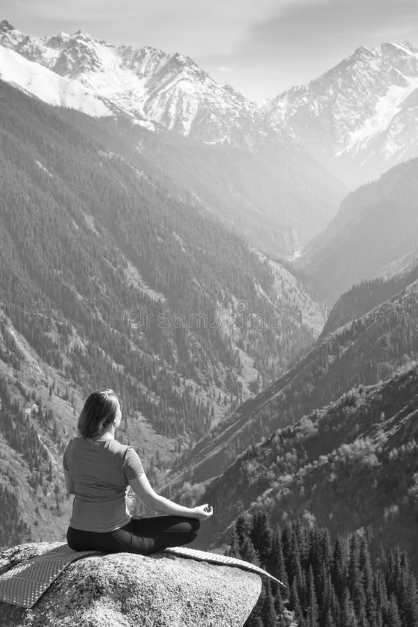 Het jonge vrouw mediteren bovenop de berg royalty-vrije stock afbeelding