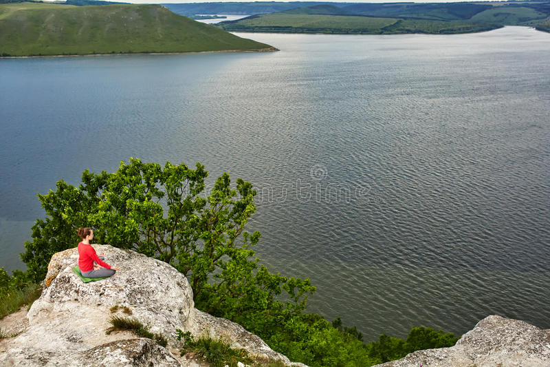 Het jonge vrouw mediteren in een lotusbloem stelt op de rots boven grote rivier stock afbeeldingen